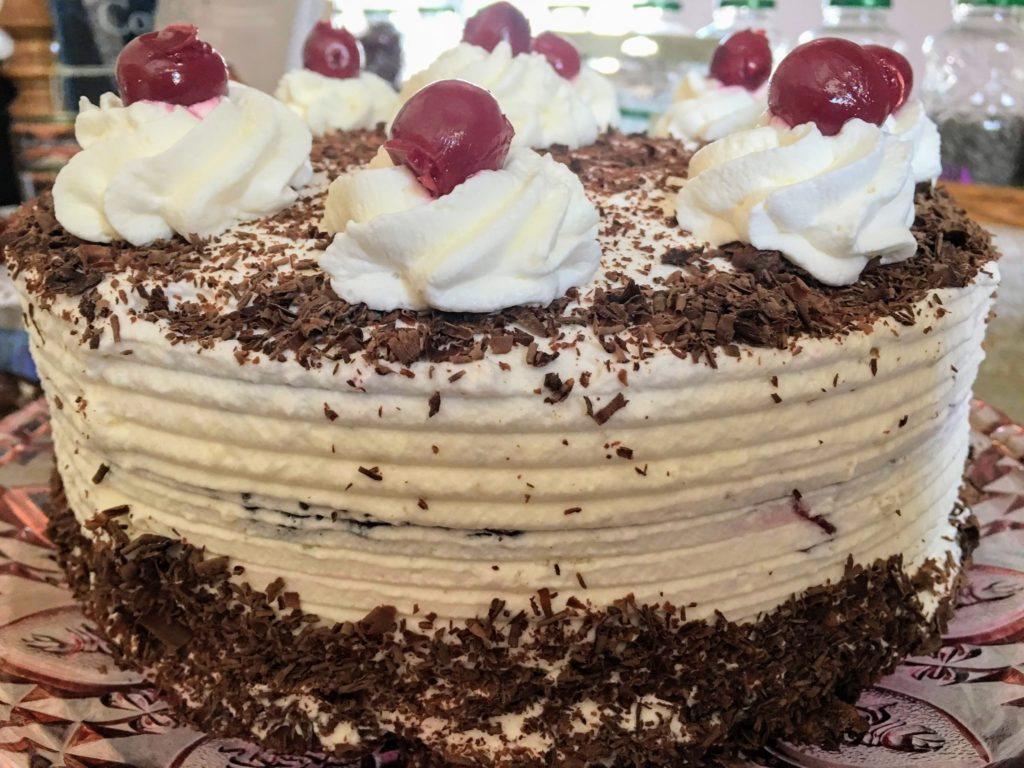 black forest cake with chocolate genoise pitted red sour cherries whipped cream and chocolate shavings from scratch