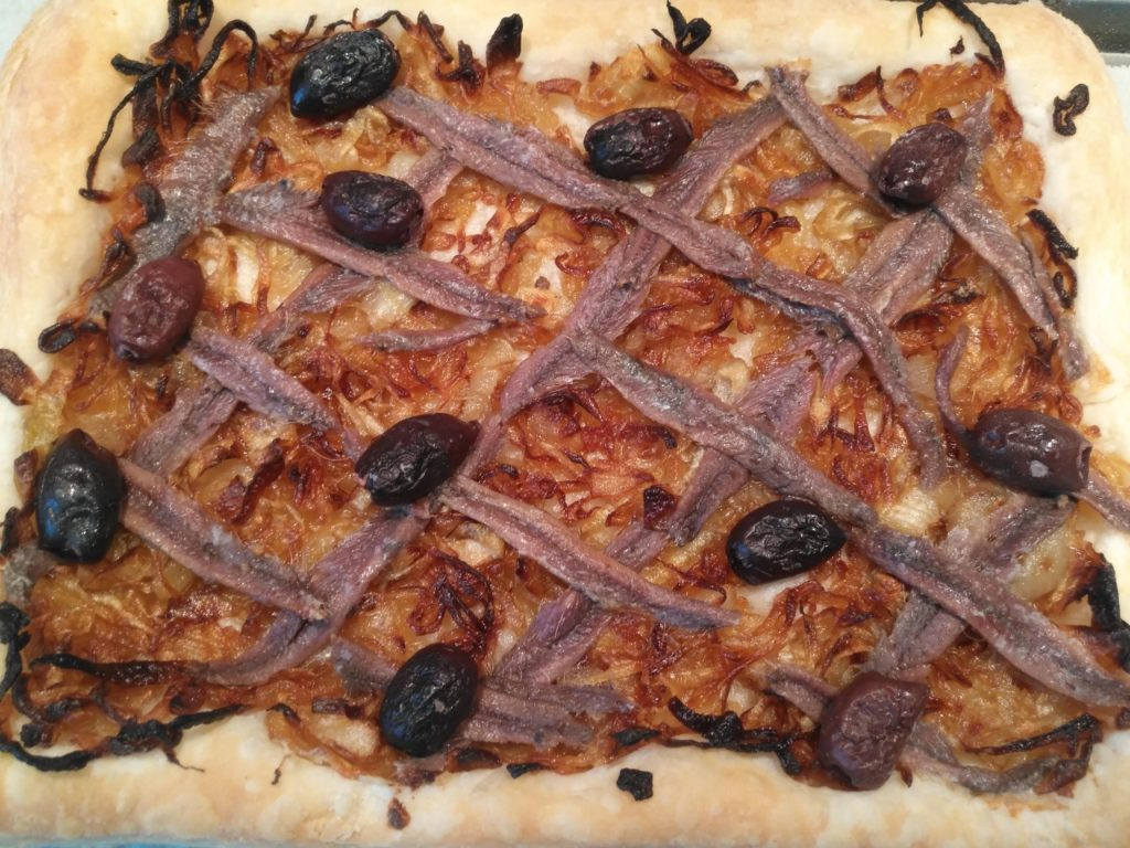 Southern France appetizer with puff pastry, caramelized onions, anchovies and black olives