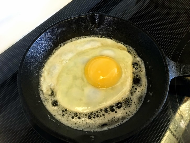frying an egg in a small cast iron pan