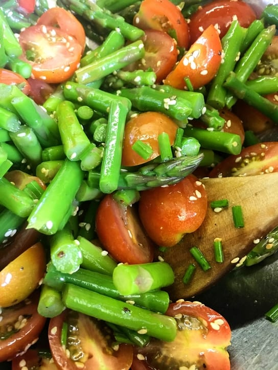mixing asparagus and cherry tomato salad